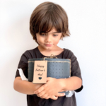 Midi Succulent mix in a charcoal handmade pot, midi jungle cacti mix held in young boys hands with personalised gift card. Biodegradable and recycled pot. Long-lasting and sustainable plant gift.